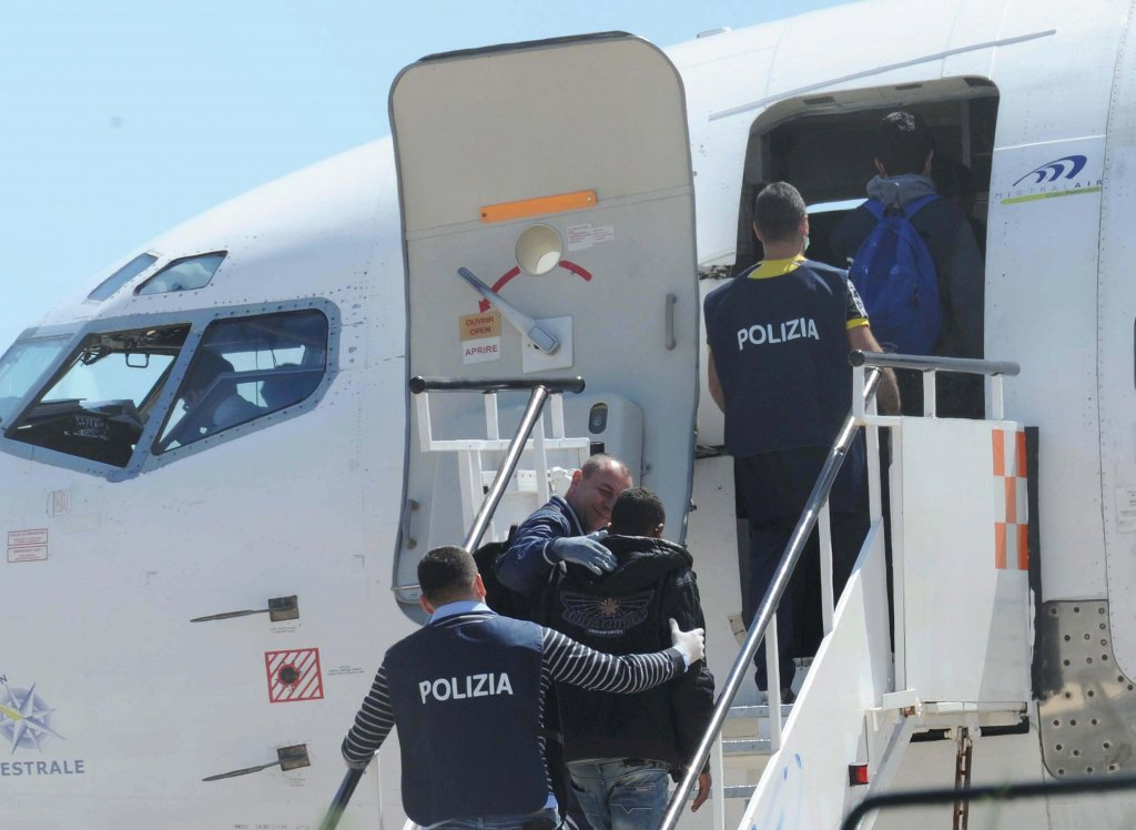 Italian police officers escort migrants onto an airplane in Lampedusa, Italy | Photo: EPA/Carlo Ferraro