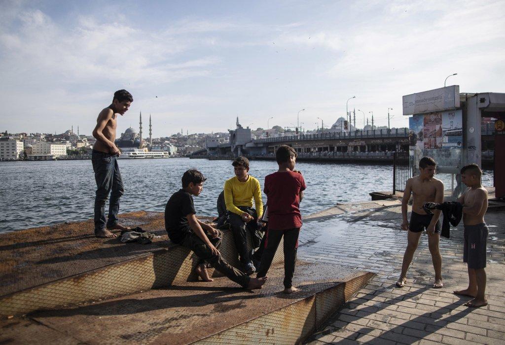 الصورة: أطفال سوريون لاجئون يستمتعون بالطقس الدافئ على شاطئ البوسفور في إسطنبول. المصدر: أنسا/ إي بي إيه/ إردام شاهين.