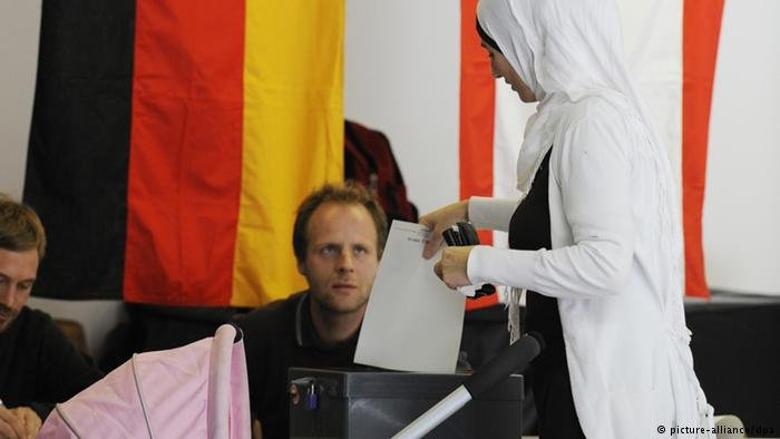 A  women in hijab casting her vote in Germany