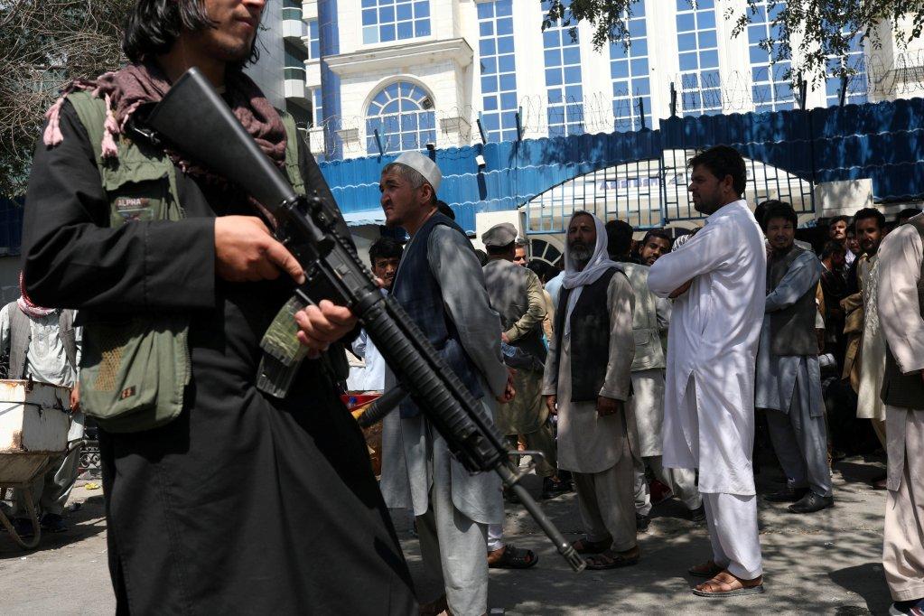 Un Taliban armé surveille des personnes faisant la queue devant une banque de Kaboul, le 4 septembre 2021. Crédit : Reuters