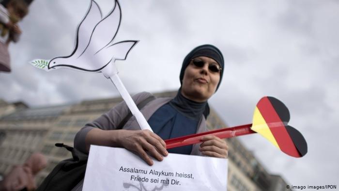 "imago images/IPON  سيدة تحمل بيدها علم ألمانيا وبالأخرى رسما لحمامة السلام مع يافطة كتبت عليها السلام عليكم، في مسيرة ضد ""معاداة المسلمين"" في برلين (23/6/2017)"