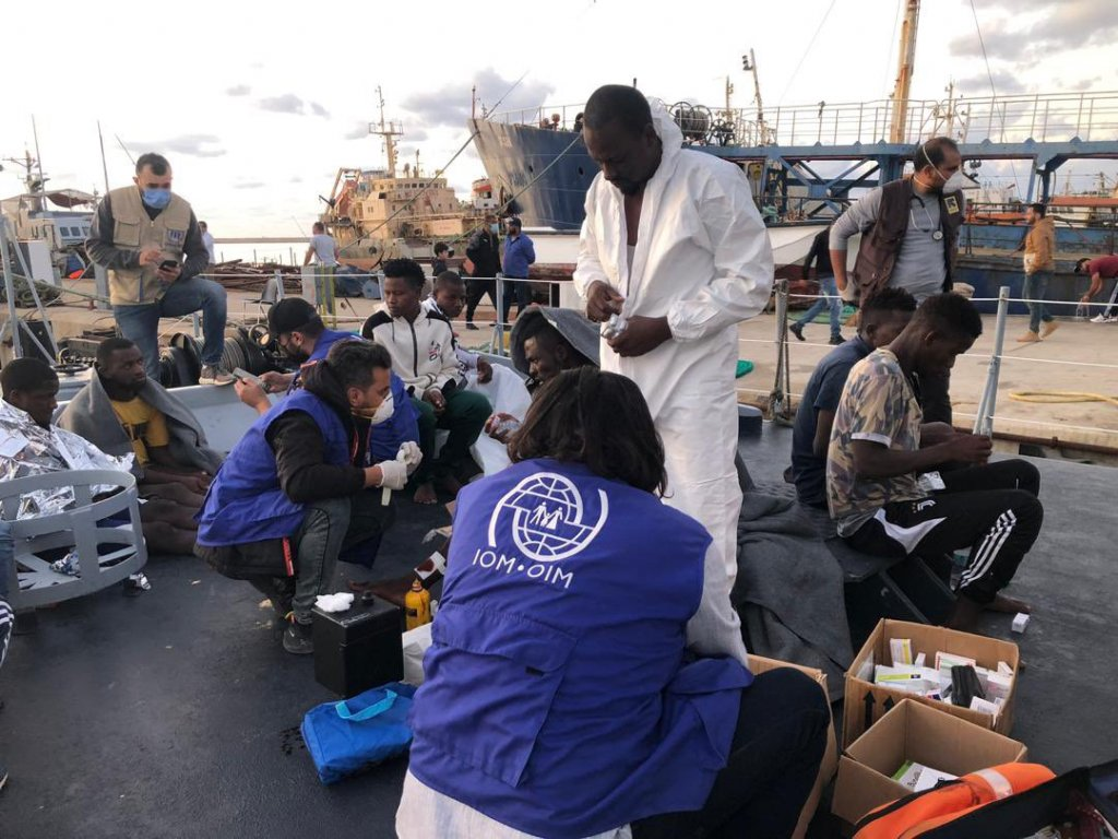IOM staff helping a group of migrants rescued at sea | Credit: IOM Twitter account
