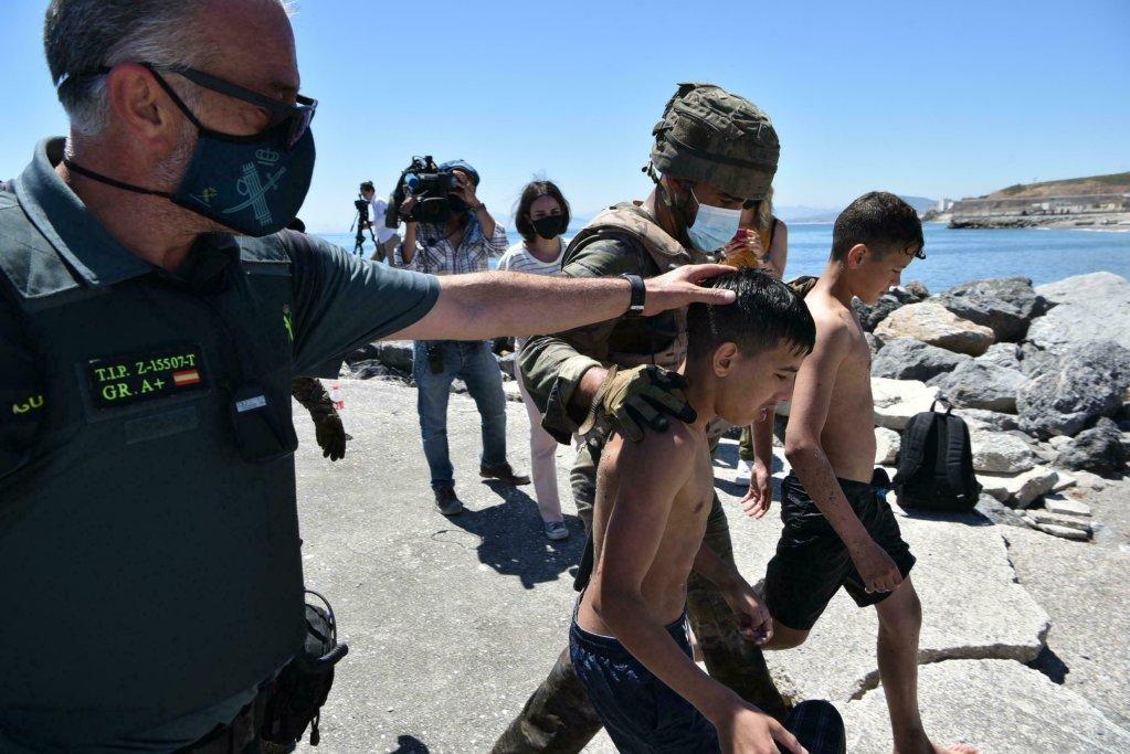 © أ ف ب/ أرشيف  صورة بتاريخ 19 أيار/مايو 2021 تظهر عسكريا وعنصرا من الدفاع المدني الإسبانيين يرافقان مهاجرين قاصرين وصلا سباحة إلى جيب سبتة الإسباني