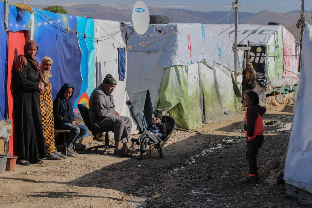 Syrian refugee families sitting in front of their tents in Gazza village in the Beqaa Valley, Lebanon | Photo: EPA/Nabil Mounzer