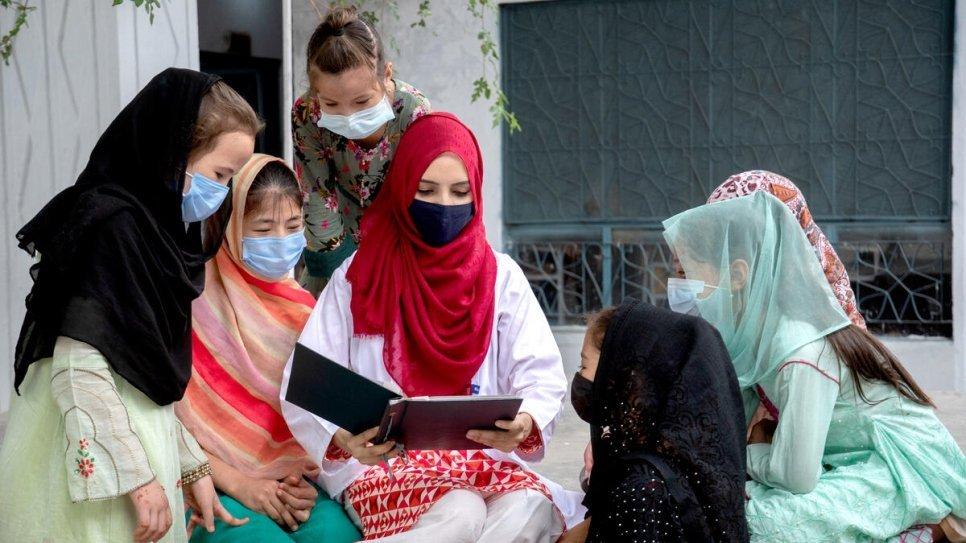 ۲۹ کلنه سلیمه په خپله سیمه کې نجونو ته د خپل ژوند د سفر کیسه کوي. راولپندي، پاکستان. انځور: UNHCR
