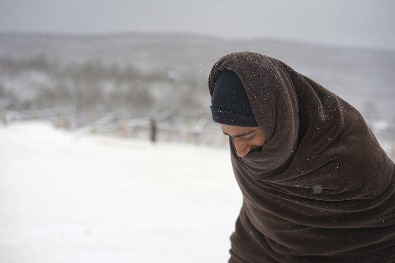 بوسنیا کې د لیپا کمپ ته څیرمه د سختو واور له منځه یو کډوال تیریږي. انځور:اسوشیدتید پرس. ۲۶ ډسمبر ۲۰۲۰