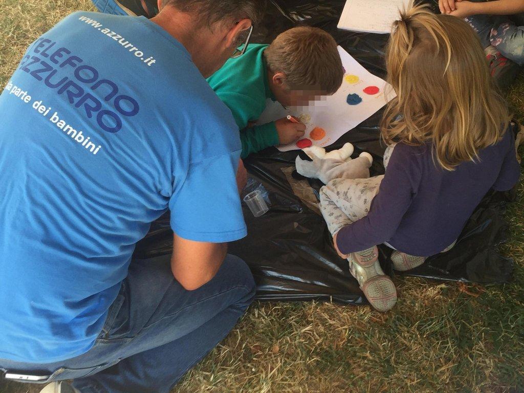 """متطوع من """"تليفونو أتزورو"""" داخل مخيم للأطفال في المناطق التي تعرضت لزلزال في العام 2016. المصدر: أنسا / تليفونو أتزورو."""
