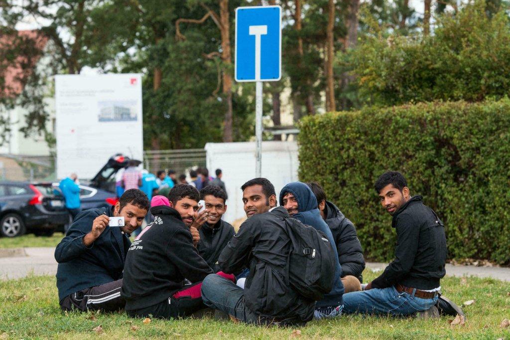AFP - PATRICK PLEUL |Des réfugiés pakistanais sur la pelouse du centre d'enregistrement des réfugiés à Eisenhüttenstadt, le 9 septembre 2015.