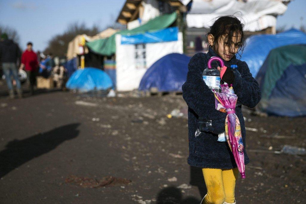 """Ansa / طفلة كردية تسير في مخيم المهاجرين في كاليه قبل تفكيكه. المصدر: """"إيه بي إيه"""" / صورة من الأرشيف."""