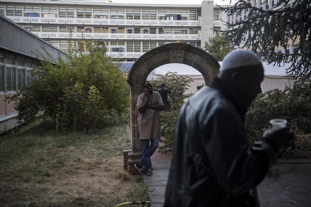 Migrants wait in the yard of an unoccupied building of the 'Agence nationale pour la formation professionnelle des adultes' (AFPA), in the Paris suburb of Montreuil. Photo: EPA/JULIEN DE ROSA