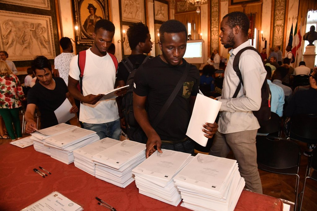 Young men take a copy of the Italian Constitution translated into English, French, and Arabic, during the first course for migrant asylum seekers. PHOTO/ARCHIVE/ANSA/LUCA ZENNARO