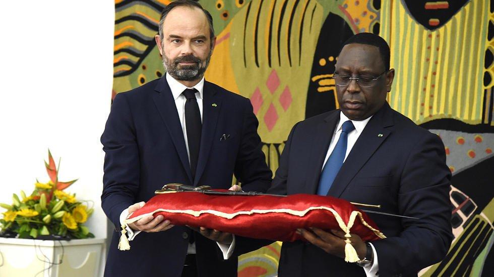 Seyllou / AFP |Le président sénégalais Macky Sall reçoit le sabre El Hadj Oumar Tall des mains d'Edouard Philippe, au palais présidentiel à Dakar, le 17 novembre 2019.