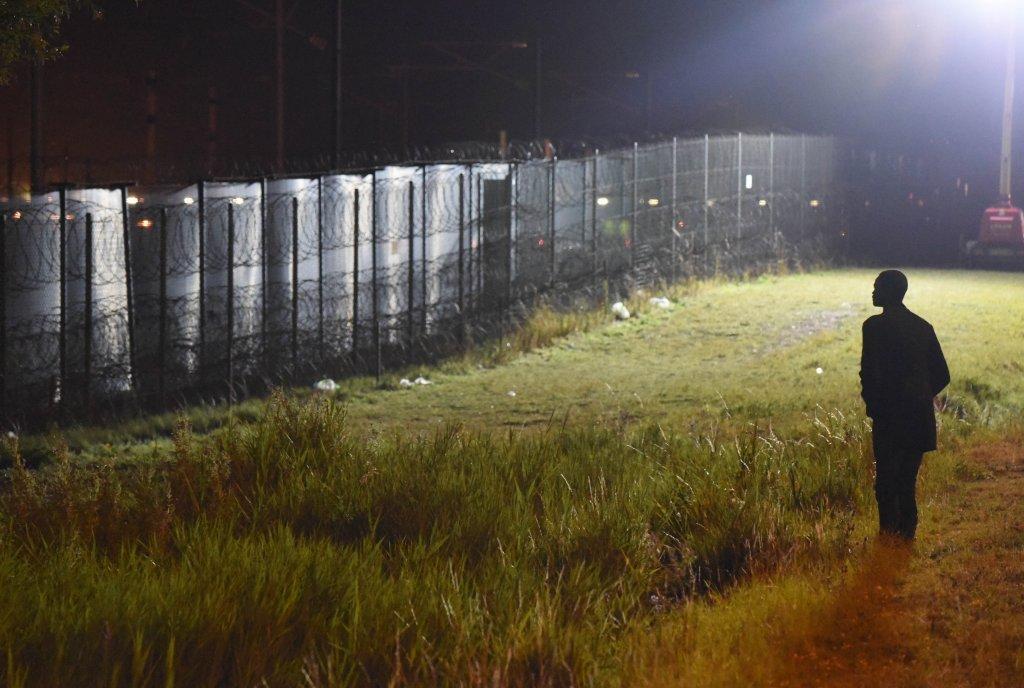 یک مهاجر در برابر در نزدیکی جادهای در کاله که با دیوار بلندی احاطه شده است.