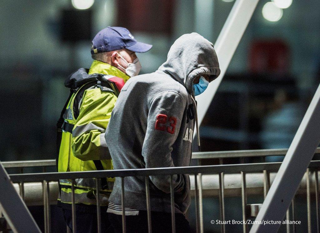 Un migrant accompagné d'un agent britannique à Douvres, après avoir traversé la Manche. Crédit : Picture alliance