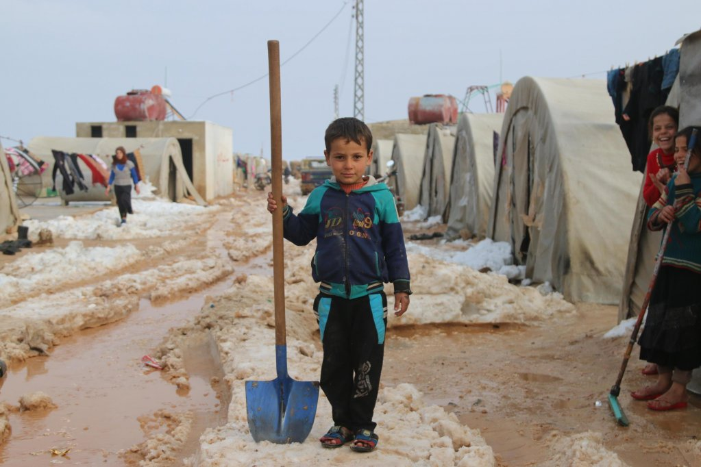 Radwan, 6, holds a shovel in front of his family's tent in the Al-Nour IDP camp in rural Idlib, Syria | Photo: ANSA/UNICEF PRESS OFFICE