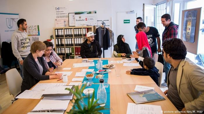 Refugee assistance workers counsel some Afghan refugees in the city of Dortmund