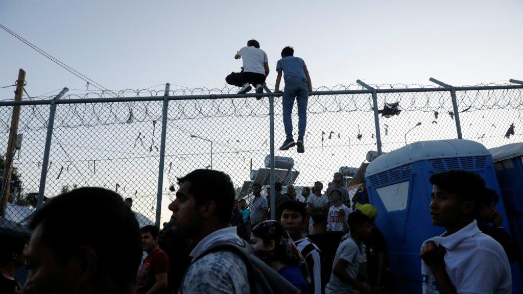 Deux migrants grimpent au sommet d'un grillage lors des émeutes dans le camp de Moria à Lesbos, le 29 septembre 2019. Crédit : Reuters