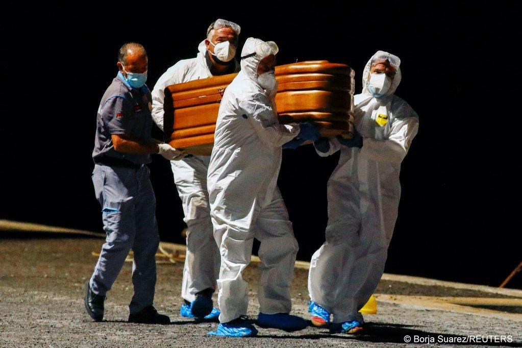رجال من الصليب الأحمر  ينقلون جثث أربعة مهاجرين إلى جزيرة هيبرو الإسبانية