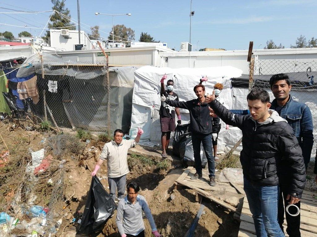 """جزء من متطوعي """"فريق موريا للتوعية بكورونا"""" أثناء حملة لتنظيف المناطق المحيطة بالمخيم. الحقوق محفوظة"""