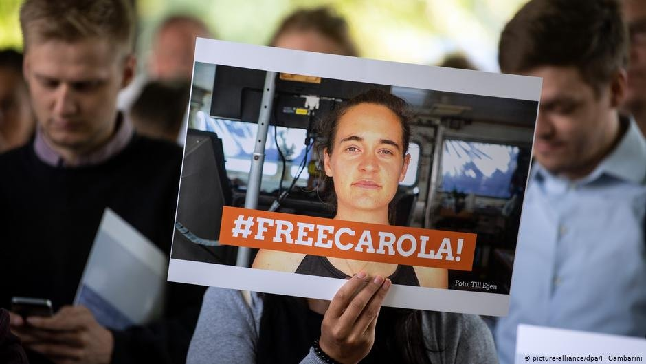 "Demonstrators holding up a sign ""#FreeCarola"" 