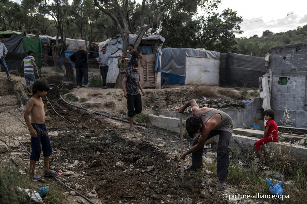 A migrant digs a hole in a temporary camp next to the Moria refugee camp on the Greek Aegean island of Lesbos on June 21, 2020   Photo: Angelos Tzortzinis/DPA