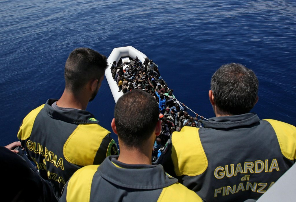 "Crew members of the P.03 ""Denaro"" ship of the Italian financial police during the transfer of hundreds of migrants off the coast of Libya 