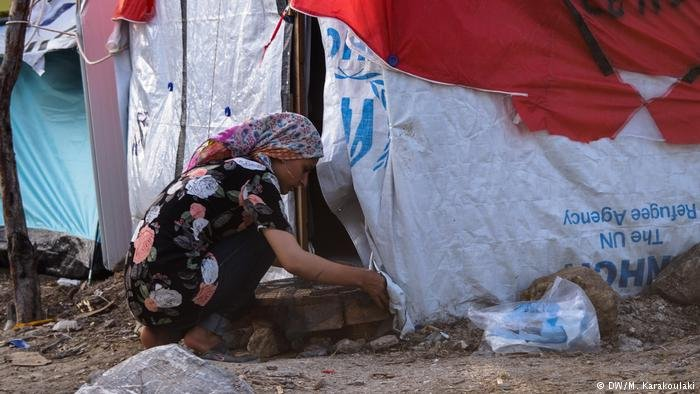 A woman prepares a makeshift stove at a tent in Lesbos