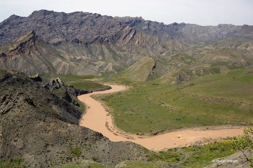 The muddy Hari Rud river, at the border between Iran and Afghanistan, winds through rocky hills brushed with spring green in Gulran District, Herat Province, Herat Afghanistan | Photo: Imago Images