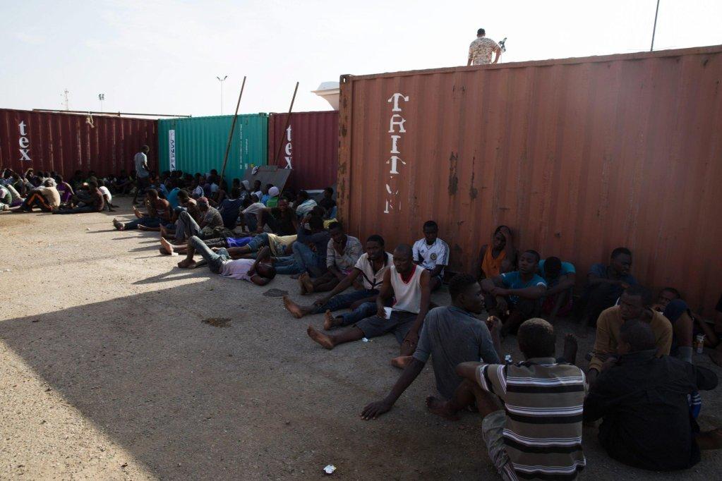 ANSA / مهاجرون تم إنقاذهم بالقرب من السواحل الليبية يجلسون في ميناء طرابلس قبل نقلهم إلى مركز الاحتجاز في العاصمة الليبية. المصدر: إي بي إيه.