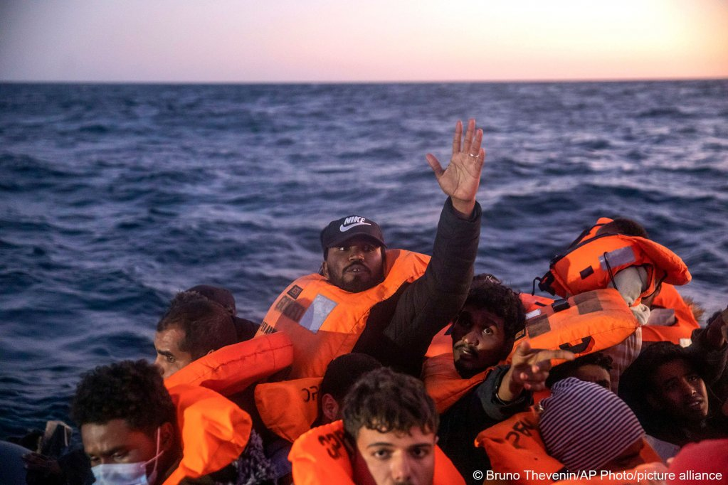 Migrants on board a rubber dinghy reach out to crew members of the Open Arms, February 12, 2021 | Photo: picture alliance/dpa/AP | Bruno Thevenin