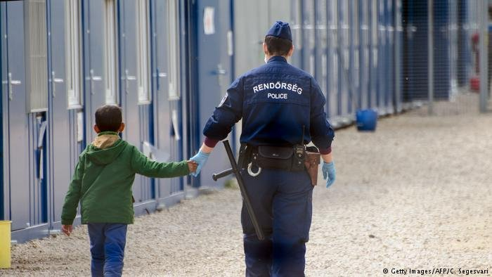 Migrant child being accompanied by authorities