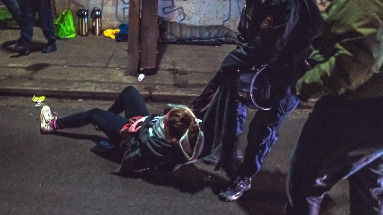 ضباط الشرطة يسحبون متظاهرة شابة من أمام مركز الترحيل في فيينا.