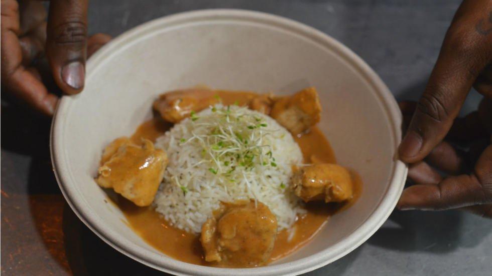 """""""Le mafé, c'est toute mon enfance"""", raconte Aboudramane, tout en dressant une assiette de ce plat subsaharien composé de riz et de poulet, nappés d'une sauce aux arachides. © Ratiba Hamzaoui / France 24"""