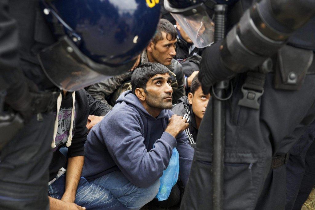 مهاجرون ينتظرون أمام ضباط الشرطة بالقرب من مدخل مركز استضافة في أواتوفاتس بكرواتيا. المصدر: إي بي إيه/ زولتان بالوج.