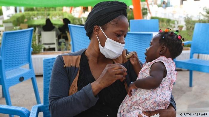 عائشة المهاجرة من غينيا مع طفلتها في حديقة بتونس