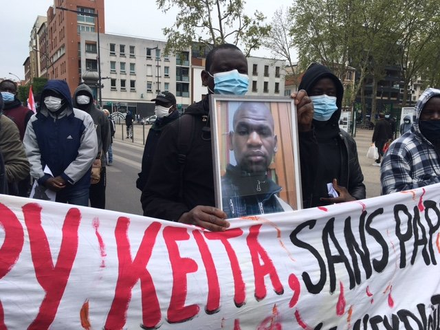 Boubou Konaté holds a photo of his cousin Bary Keita, victim of a work accident, during a tribute paid to him on May 1 in Montreuil. Photo: InfoMigrants