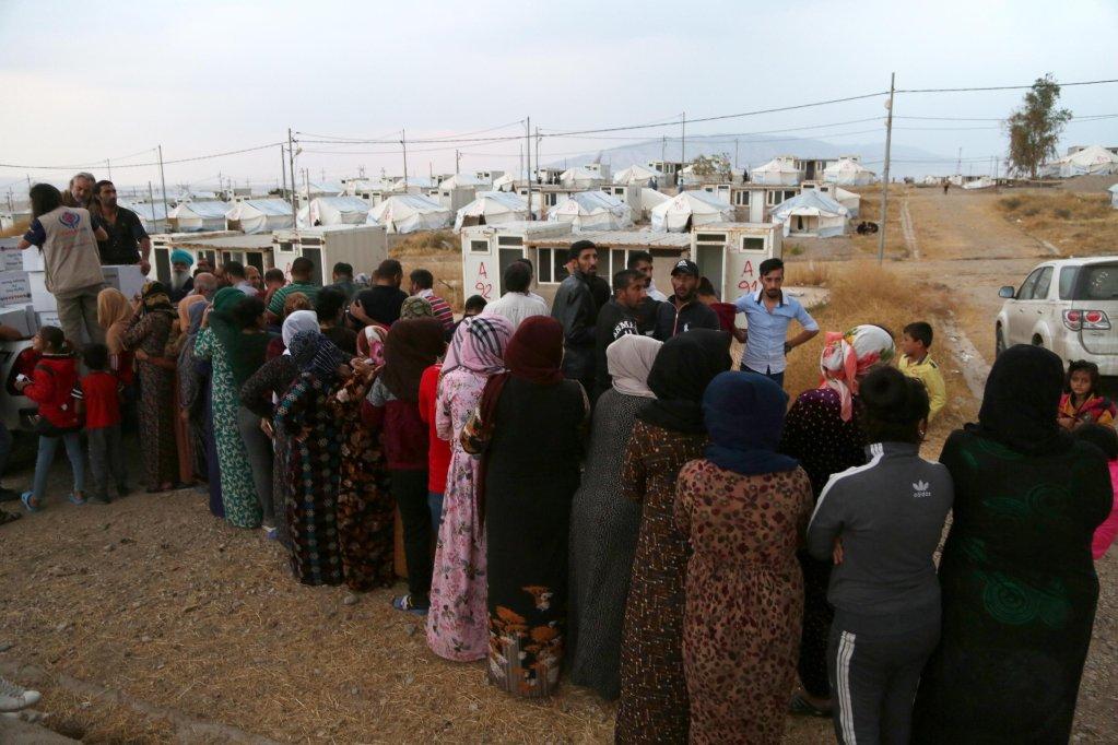 لاجئون سوريون يتدافعون للحصول على معونات غذائية في مخيم بارداراش بجنوب دهوك في إقليم كردستان العراق. المصدر: إي بي إيه/ جيلان حاجى.