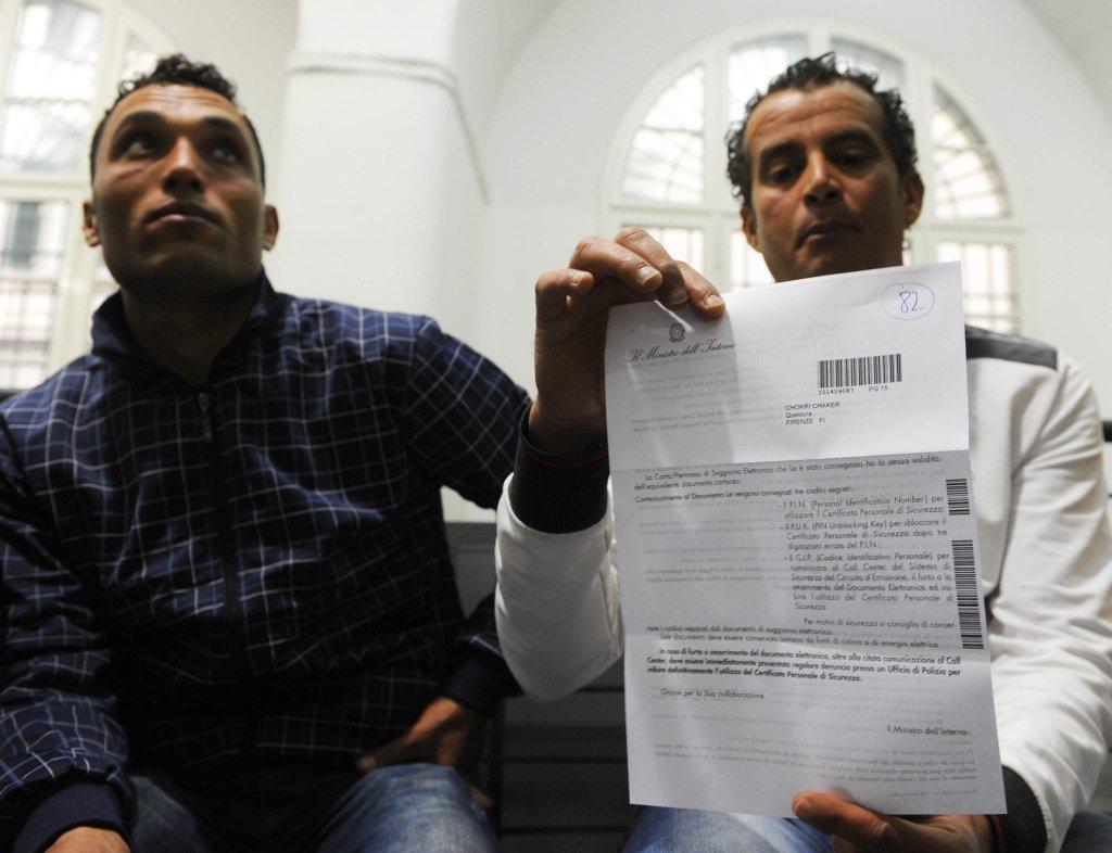 مهاجران تونسيان ينتظران في مكتب الهجرة بمركز الشرطة في فلورنسا. المصدر: أنسا / ماوريزيو ديجل إنوسينتي.