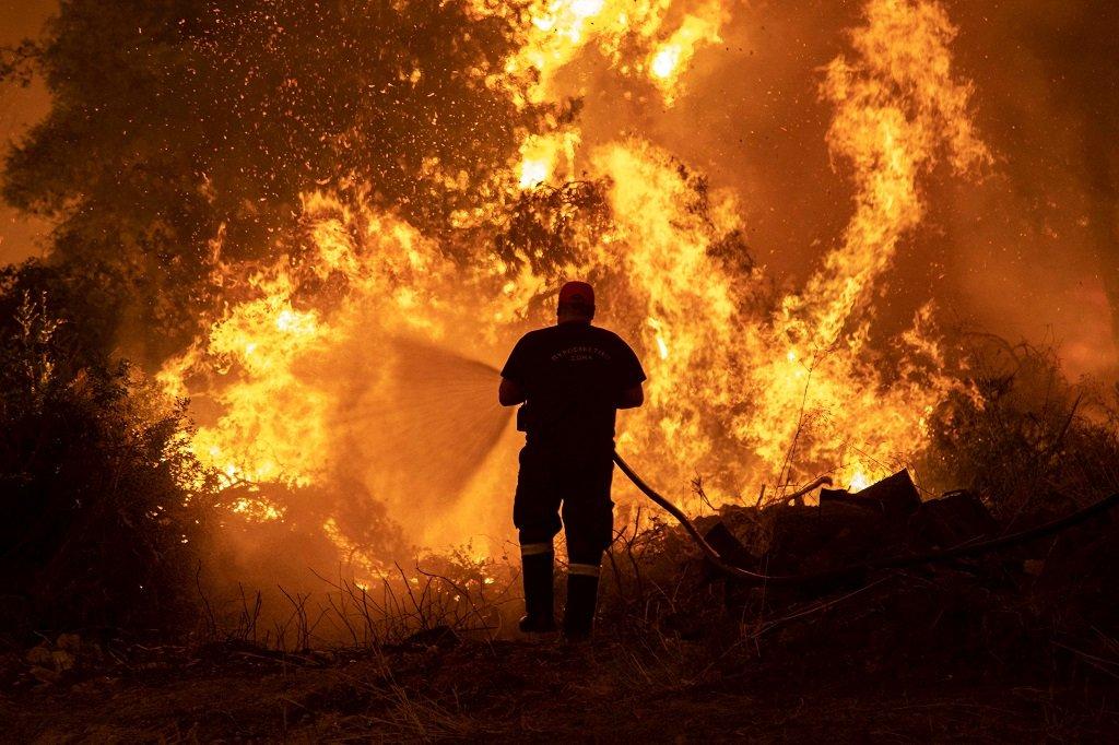 رجل إطفاء يكافح حريقا اندلع في بلدة بيفكي على جزيرة إيفيا اليونانية، 8 آب\أغسطس 2021. رويترز
