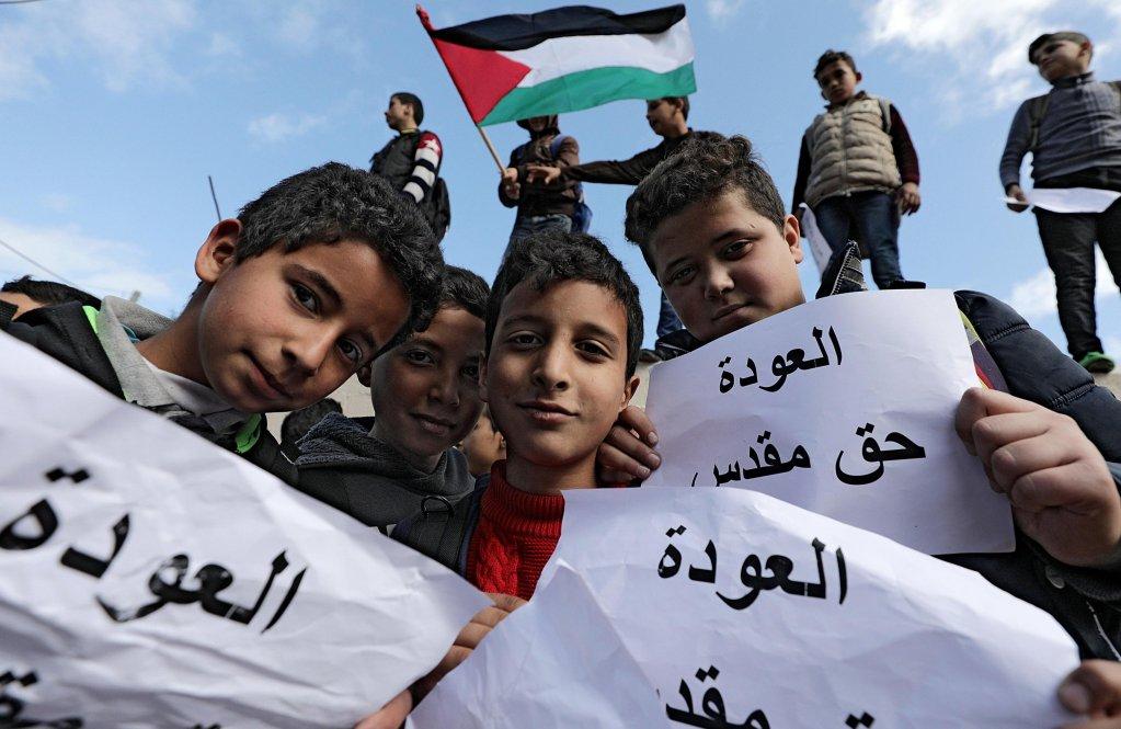 """ansa / طلاب من اللاجئين الفلسطينيين يحملون لافتة كتب عليها """"العودة حق مقدس""""، خلال احتجاج على قرار الولايات المتحدة خفض المساعدات إلى غزة. المصدر: إي بي إيه/ محمد صابر."""