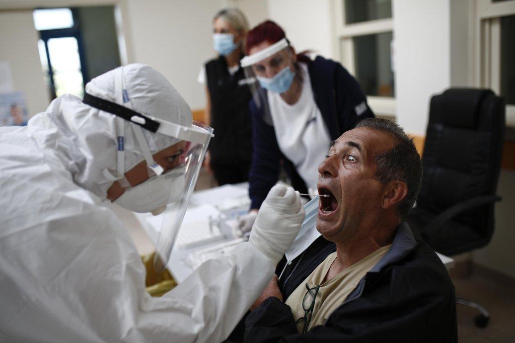 ANSA / كاترينا تريكاليوتي الموظفة بمنظمة الصحة الوطنية اليونانية (إلى اليسار) مرتدية ملابس واقية خلال قيامها بإجراء اختبار كورونا في جزيرة كوفونيسي اليونانية. المصدر: إي بي إيه/ يانيس كوليسيديس/ أنسا.