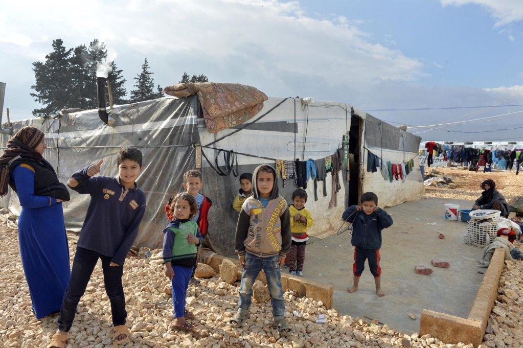 ansa / لاجئون سوريون يقفون خارج أحد الملاجئ العشوائية في مخيم حوش النبي بوادي البقاع في لبنان. المصدر: إي بي أيه/ وائل حمزة
