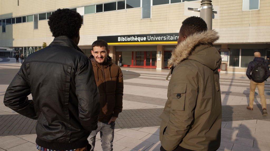 نهاد، 21 عاما، أحد المشاركين في برنامج جامعة ليل الفرنسية مثل أي طالب آخر أمام مبنى مكتبة الجامعة. حقوق الصورة جوليا دومون/ مهاجر نيوز