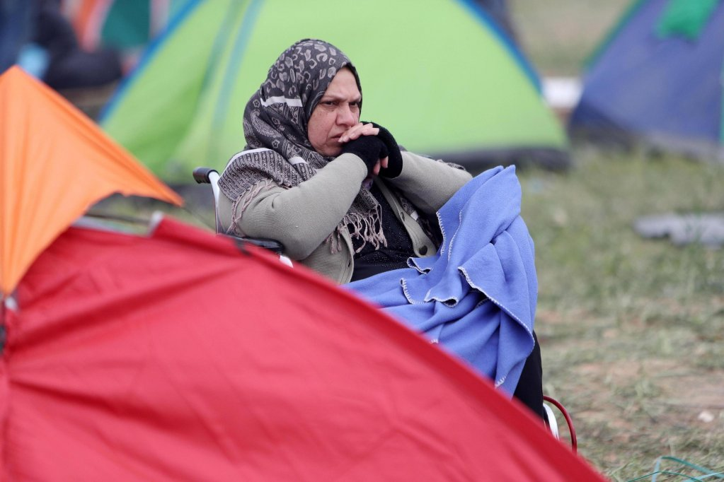 A refugee woman outside her tent in a makeshift camp, near a state run refugee camp, in the village of Diavata, west of Thessaloniki, in northern Greece | Photo: EPA/Sotiris Barbarousis