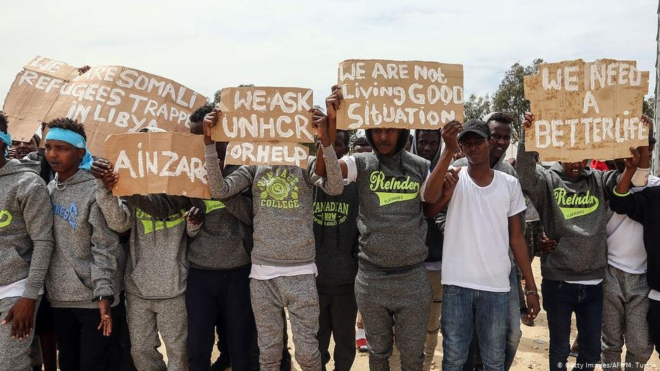 Migrants hold placards during United Nations Secretary-General Antonio Guterres' visit to Ain Zara detention  centre for migrants in the Libyan capital Tripoli | Photo: Getty Images/AFP/M.Turkla