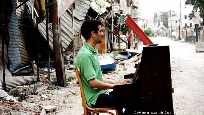 أيهم أحمد يعزف على البيانون في مخيم اليرموك وسط الخراب والدمار