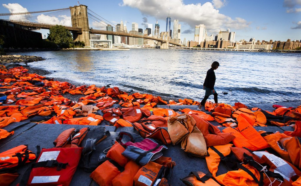 A woman walks past hundreds of refugee life jackets collected from the beaches of Chios, Greece, on the edge of the East River, to call attention to the refugee crisis in Brooklyn, New York, USA. The life jackets which were gathered by the Oxfam organization ahead of next week's United Nations Summit for Refugees and Migrants. | Credit: EPA, Justin Lane