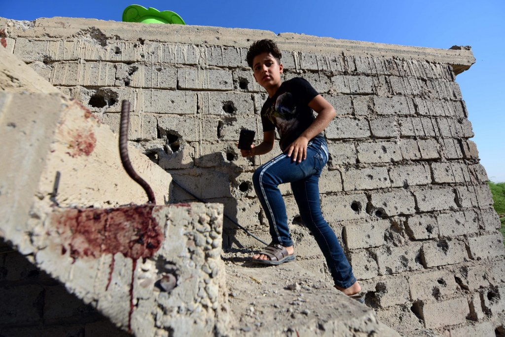 An Iraqi boy in a house damaged by bombing in the Ninewa area, where he returned to live with his family after the sudden closure by the government of several camps for displaced people | Photo: EPA/MURTAJA LATEEF