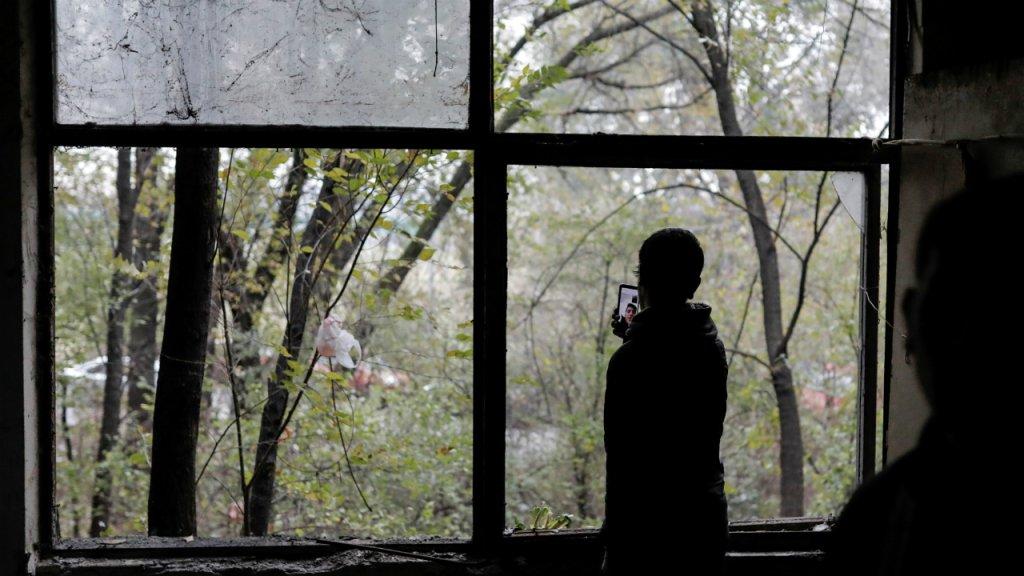 Un migrant afghan à Belgrade, en Serbie, parle au téléphone avec un ami, en décembre 2019. Photo : Reuters