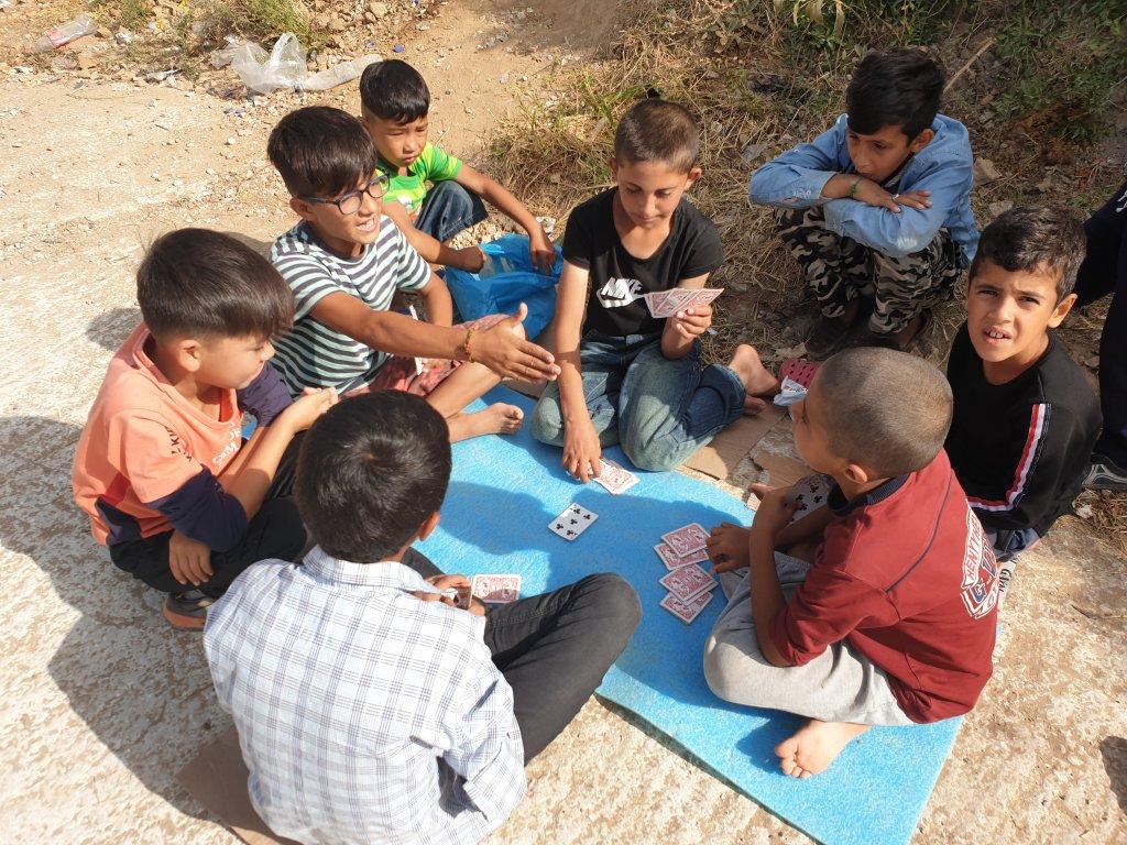 گروهی از کودکان افغان در نزدیکی کمپ موریا سرگرم بازی هستند. عکس از Amanullah Jawad